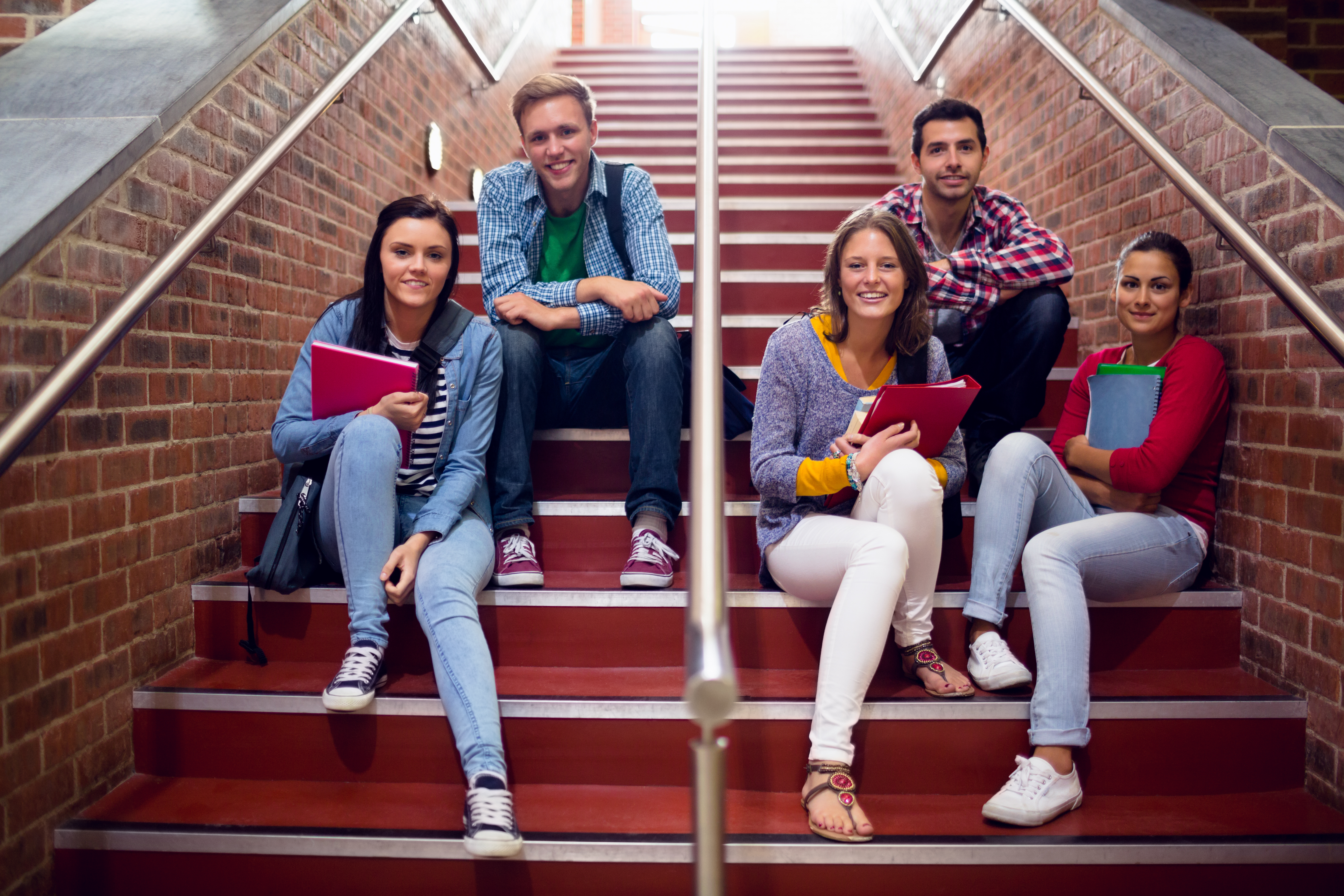 Group portrait of young college students sitting on stairs in the coll